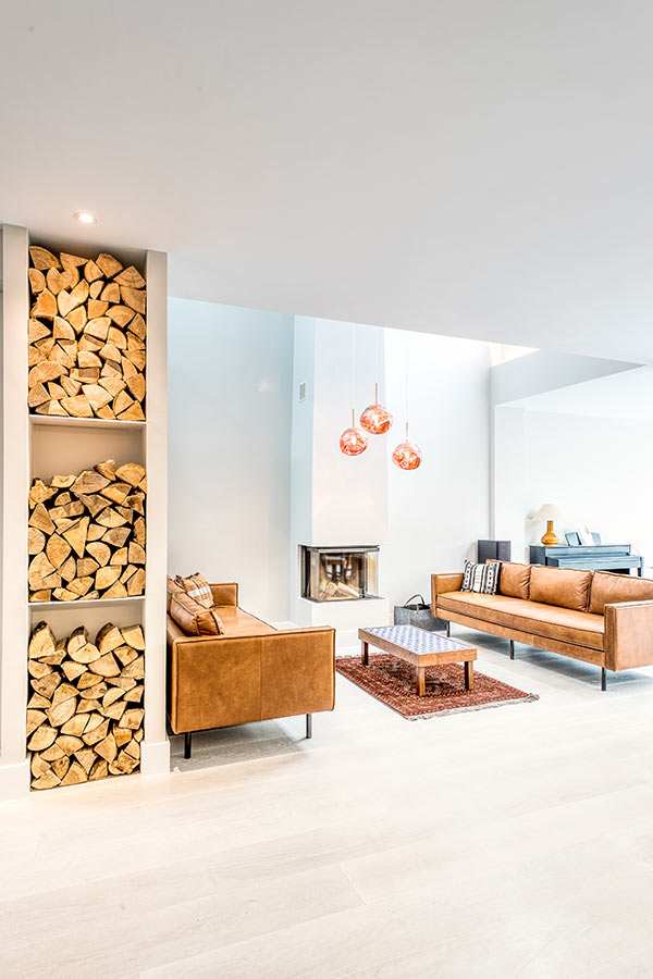 open plan living room extension in London with leather sofas and a wood burner